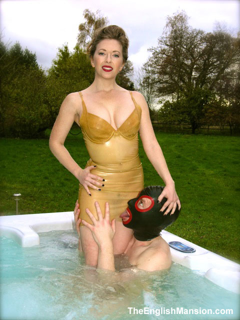 Mistress T & slave in hot tub wearing latex.
