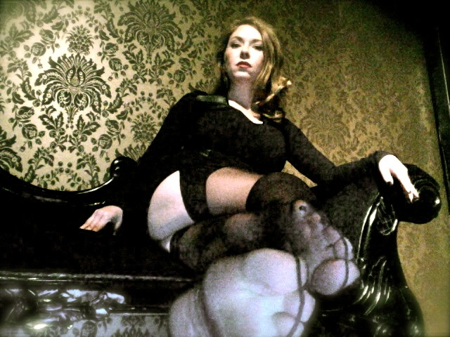 Mistress T in stockings showing feet.